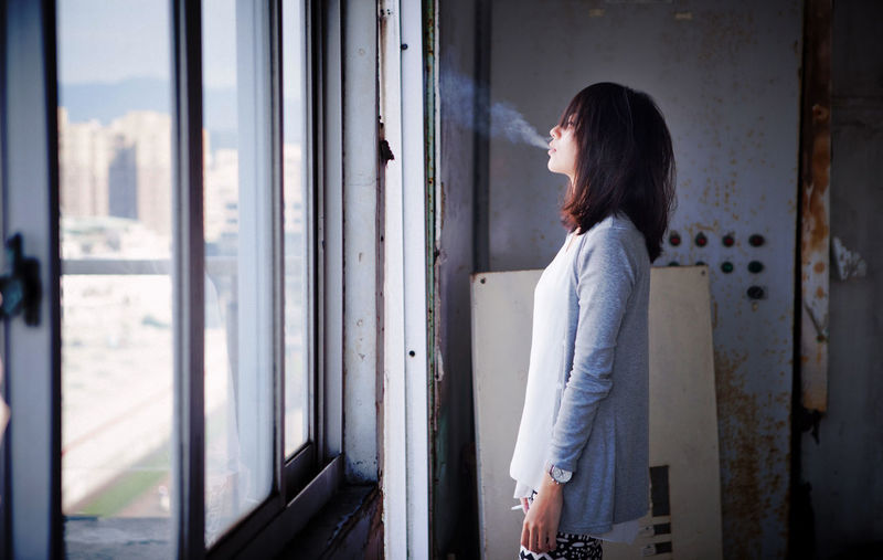 Young woman smoking in building