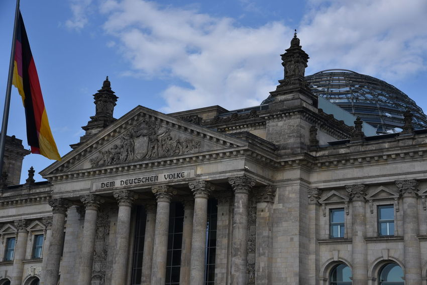 Berlin-Mitte Reichstag Berlin ReichstagBuilding Architectural Column Architecture Building Exterior Built Structure City Cloud - Sky Day Flag Government History Low Angle View No People Outdoors Reichstagskuppel Sculpture Sky Statue Tourism Travel Travel Destinations