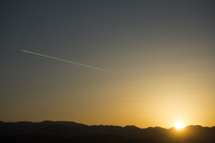 Scenic view of silhouette vapor trail against sky during sunset