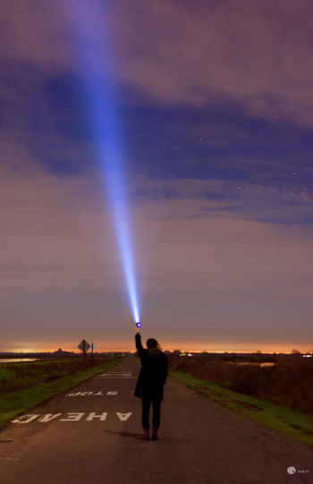 Rear view of person holding illuminated flashlight on road against cloudy sky at night