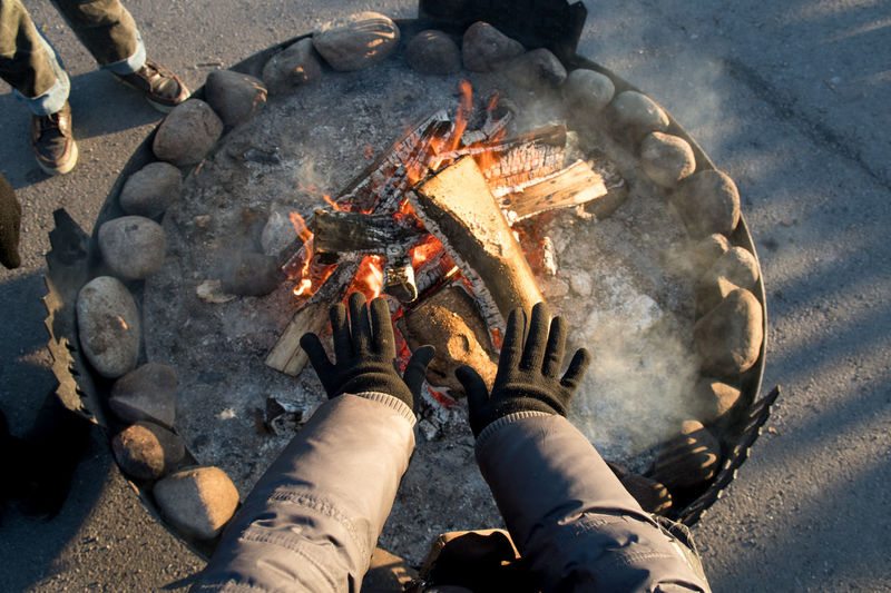 Cropped hands at fire pit during winter