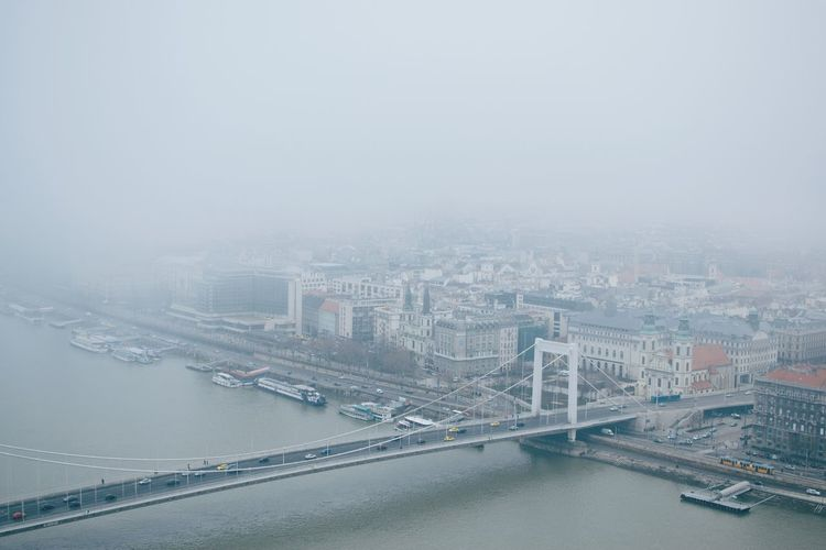 Architecture Bridge - Man Made Structure Building Exterior Built Structure City Cityscape Connection Day Fog High Angle View Modern No People Outdoors River Sky Skyscraper Suspension Bridge Transportation Travel Destinations Urban Skyline Water Shades Of Winter