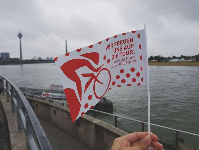 Tour de France in Düsseldorf Welcome Tour De France Tourism Cycling Race Bikes Rainy Foggy Windy Skyline Bridge Tower River Holding Flag Flag In The Wind Ships Outdoors Travel Destinations Landscape Human Hand Human Body Part Close-up City Day