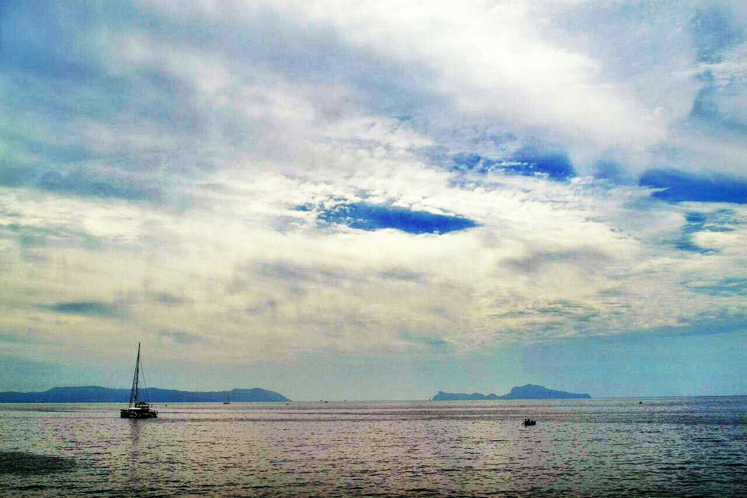 sky, sea, nautical vessel, water, transportation, waterfront, mode of transport, cloud - sky, tranquil scene, tranquility, scenics, boat, beauty in nature, cloudy, horizon over water, nature, cloud, sailing, idyllic, sailboat