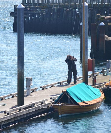 Man Photographing On Pier In Sea