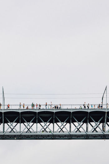 People on bridge over sea against clear sky