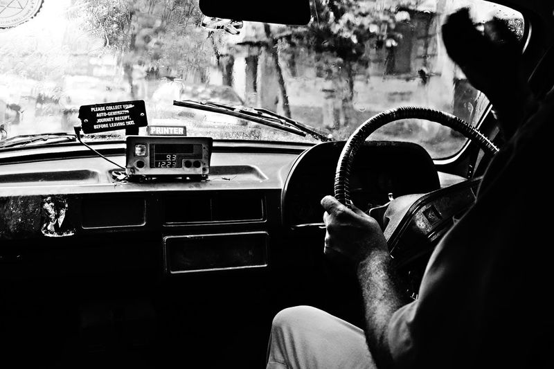Cropped image of man driving taxi