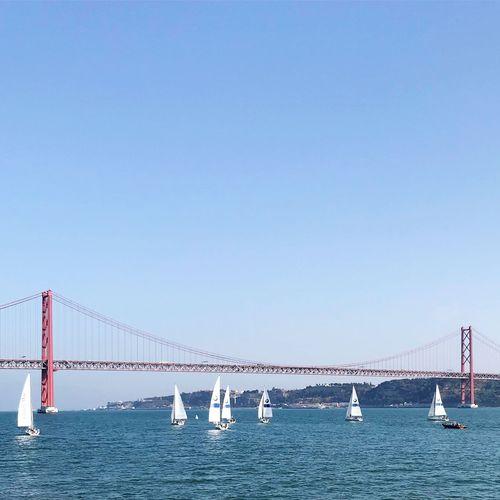 Suspension bridge over sea against clear blue sky