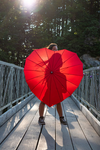 Portrait of young woman with red umbrella standing on footbridge