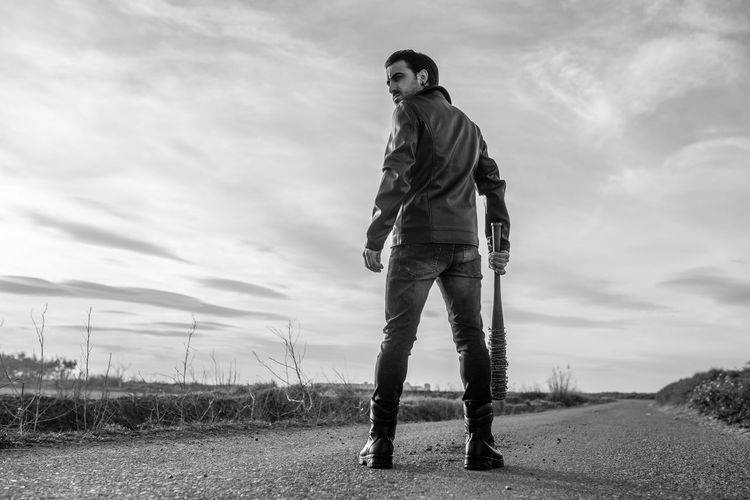Rear view of mid adult man holding barbed wire wrapped baseball bat while standing on road against sky