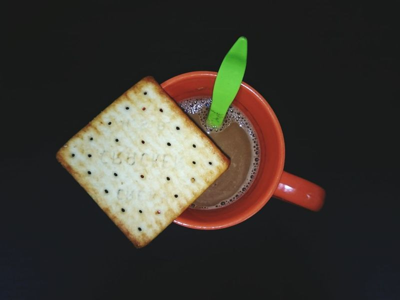 A cup of coffee with cracker Food And Drink Black Background Sweet Food Food No People Drink Freshness Indoors  Studio Shot Close-up Healthy Eating Ready-to-eat Day Cracker EmNewHere Orange Cup Green Spoon