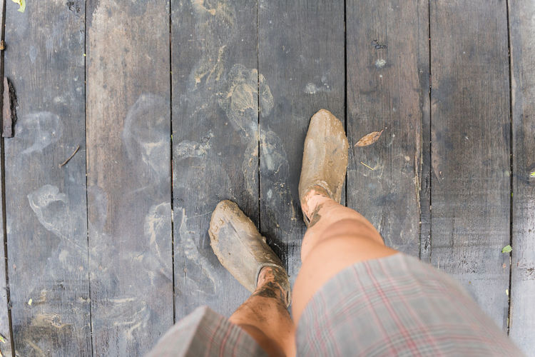 Low section of man standing on wood
