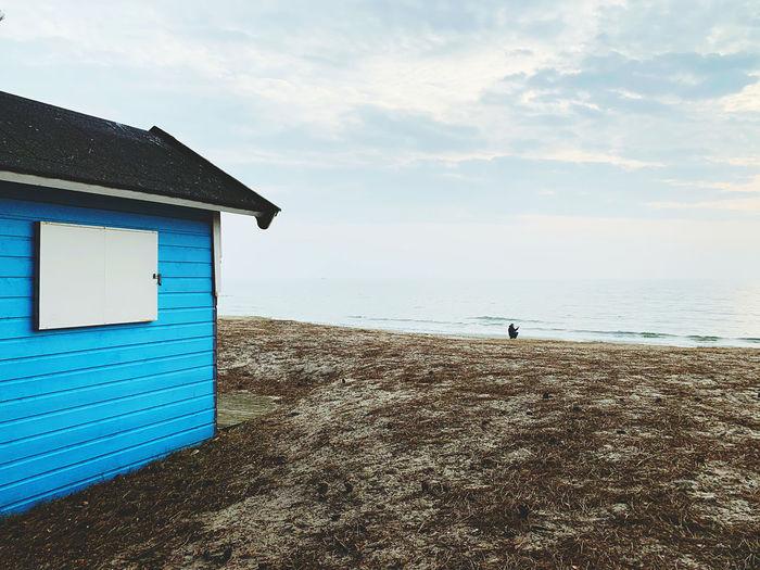 Beach hut by sea against sky