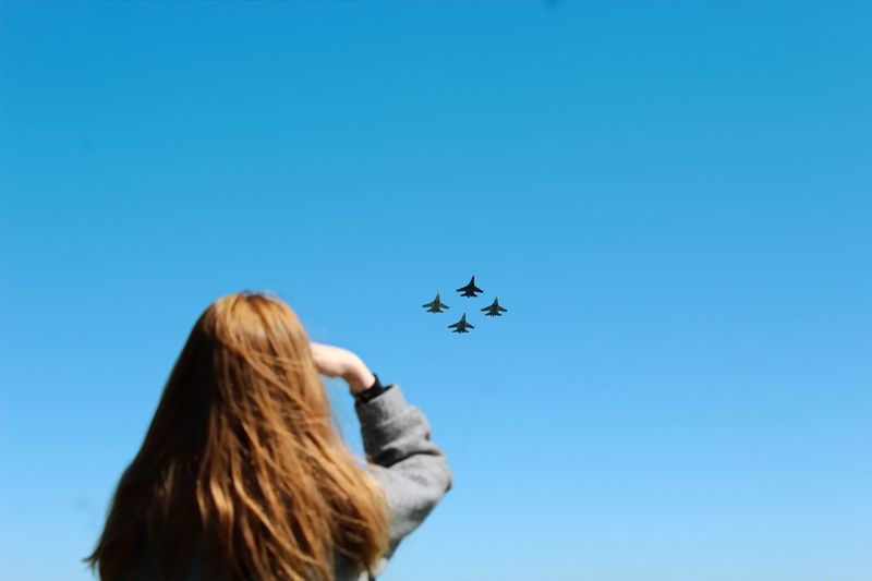 Rear View Of Woman Looking At Fighter Planes Flying In Clear Blue Sky During Sunny Day