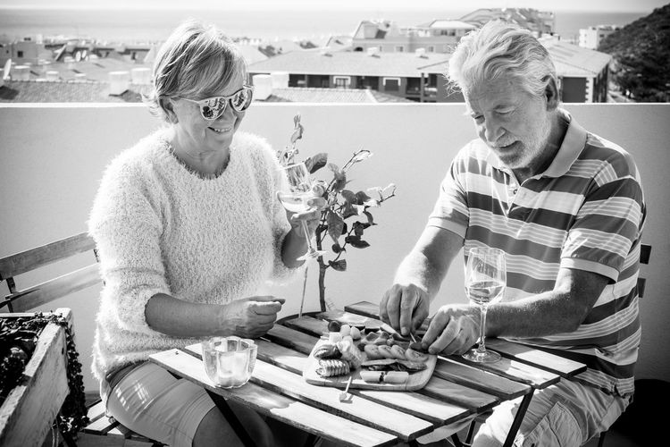 Senior Couple Having Food While Sitting In Balcony