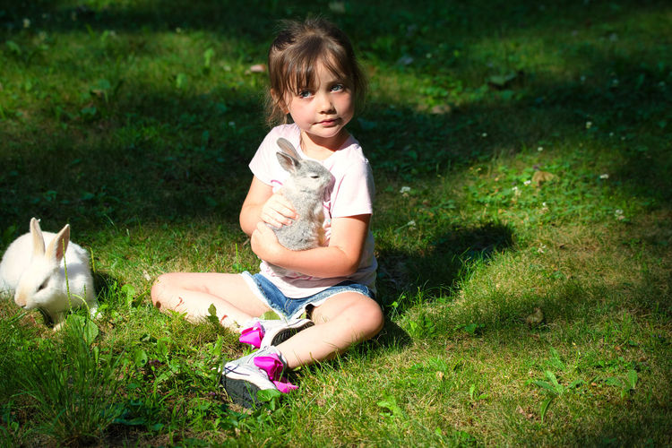 Full length of girl with rabbit sitting on field