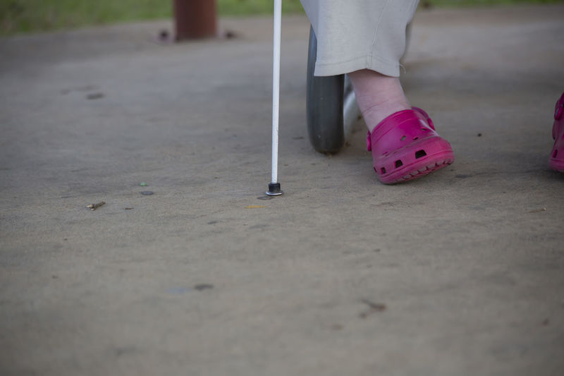Low section of blind man with cane walking on road