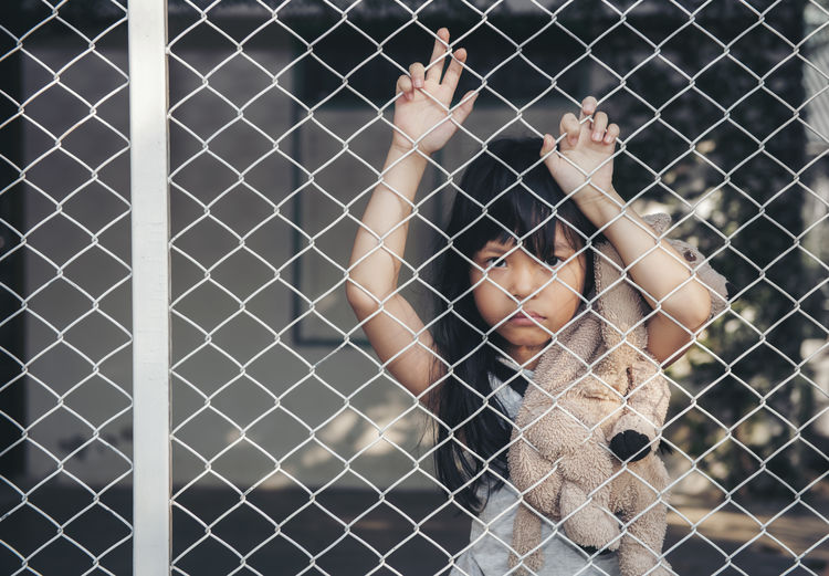 Portrait of girl with toy seen through chain-link fence