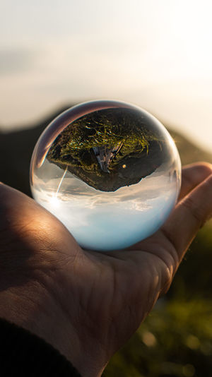 Cropped hand of person holding crystal ball against sky