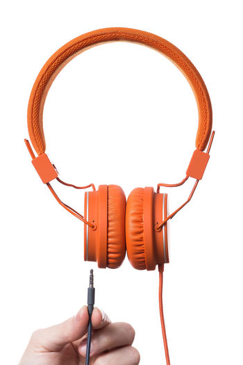 Orange Headphones on white Background Cable Close-up Headphones Holding Human Body Part Human Hand One Person People Product Product Photography Real People Sound Studio Shot Technology White Background