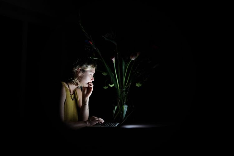 Young woman using laptop by vase on table in darkroom