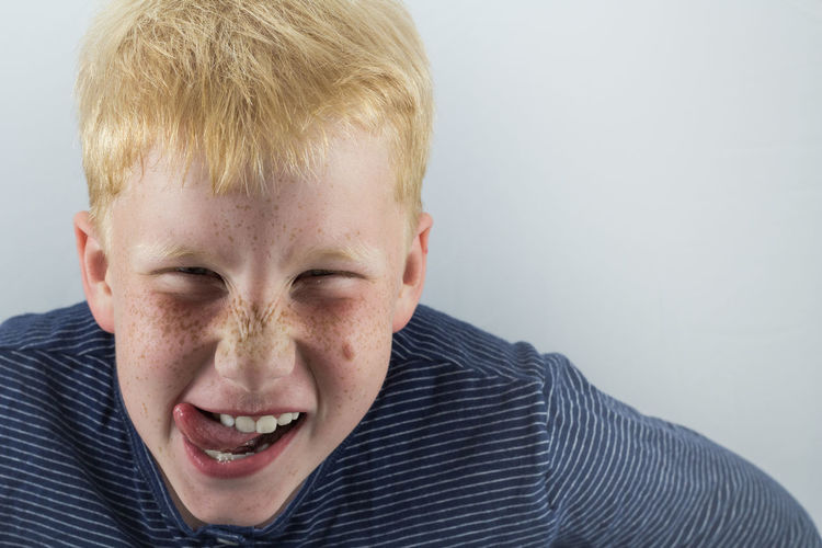 Close-up portrait of boy against white background