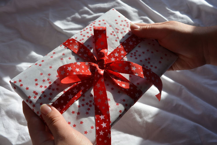 Cropped Image Of Hands Holding Christmas Present