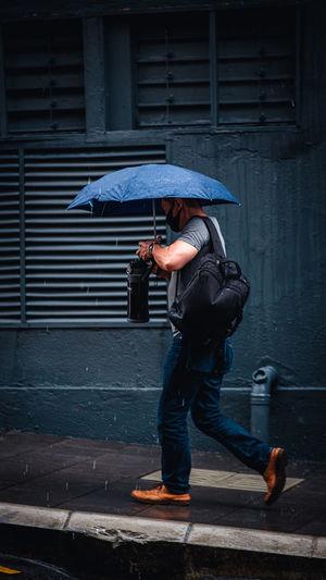 Full length of man holding umbrella on street