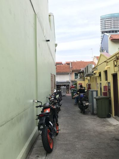 Motor scooter on road amidst buildings in city