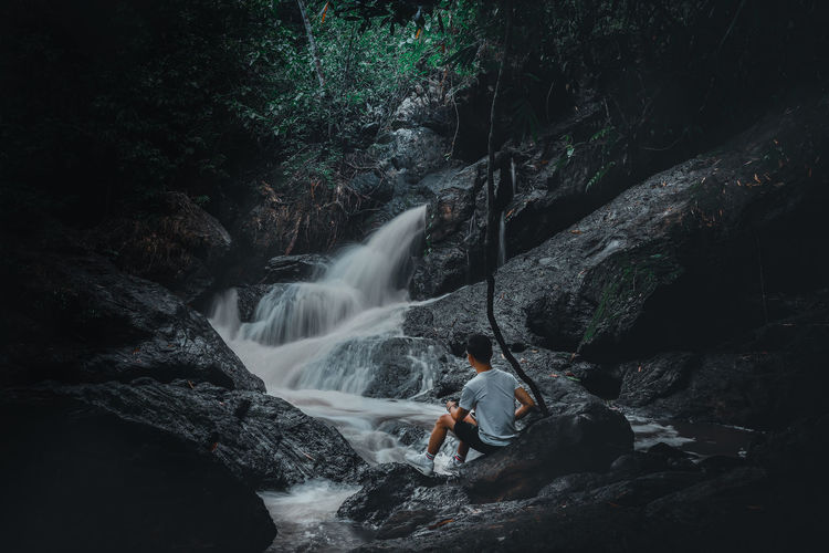 Man sitting on the rock looking at the waterfall background