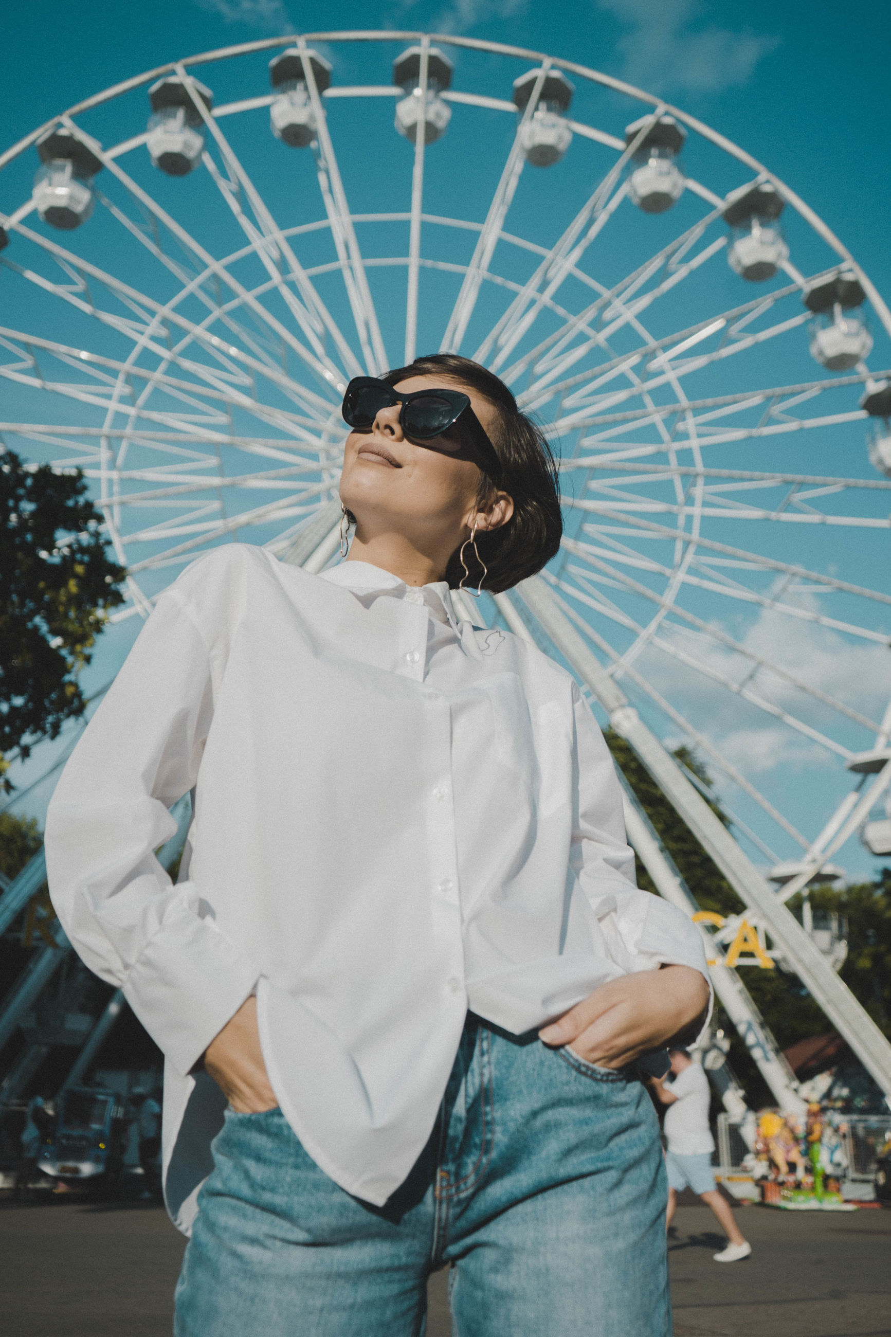 amusement park, amusement park ride, three quarter length, front view, standing, leisure activity, ferris wheel, one person, casual clothing, real people, arts culture and entertainment, young adult, women, lifestyles, females, glasses, clothing, holding, contemplation