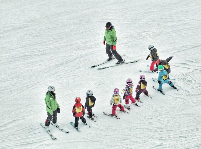 High angle view of ski instructors with students on snow