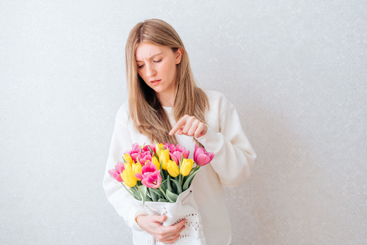 Woman holding pink flower against white background