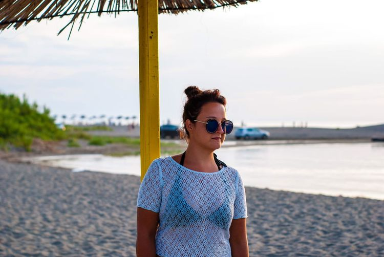 Young woman wearing sunglasses standing at beach against sky