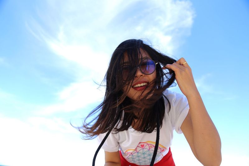 Low angle portrait of woman wearing sunglasses standing against sky
