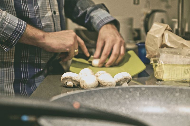 Midsection of man cutting mushrooms on table at home