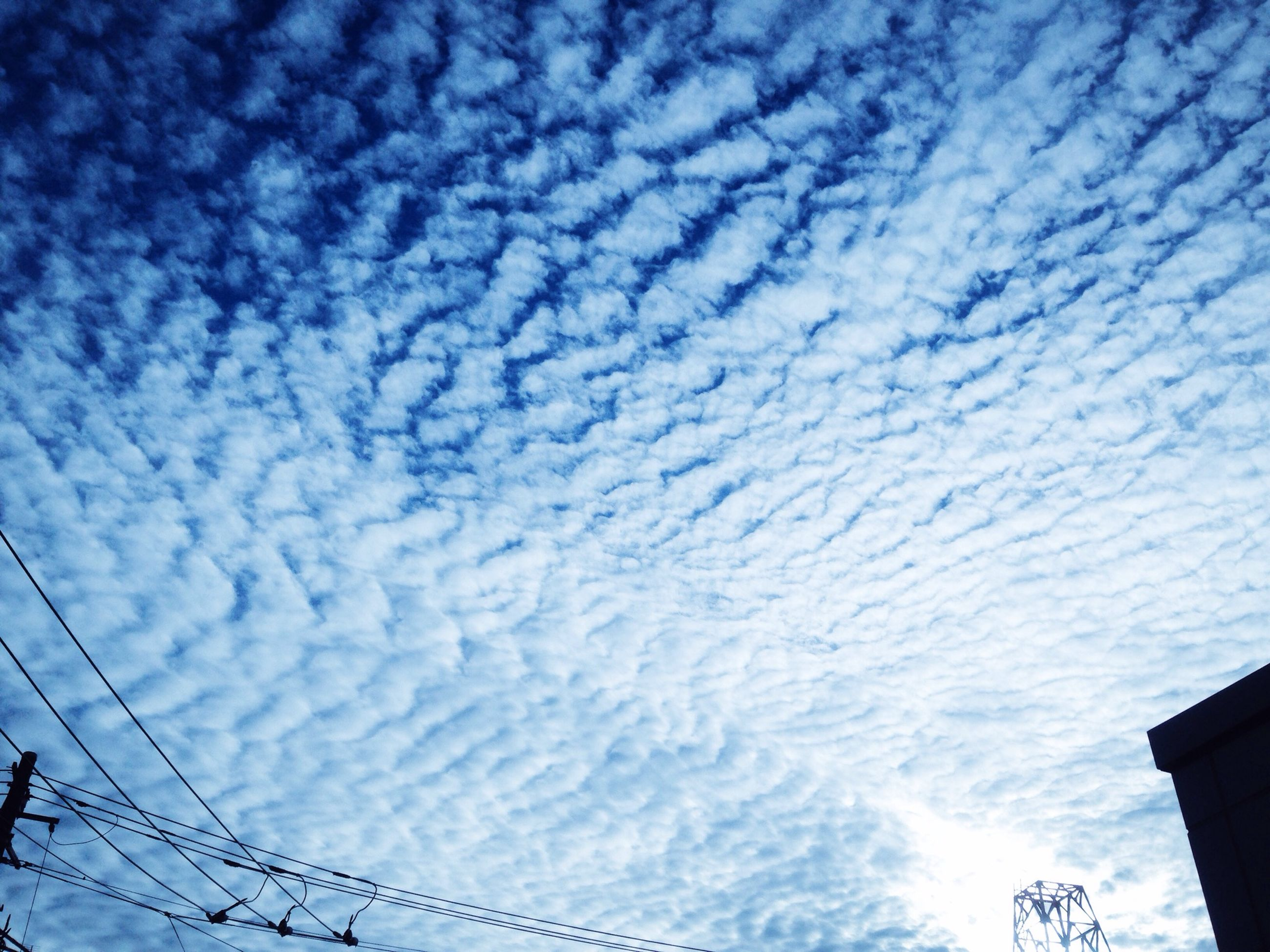 low angle view, sky, cloud - sky, built structure, architecture, blue, power line, cloudy, building exterior, cloud, electricity, cable, high section, silhouette, connection, outdoors, no people, electricity pylon, nature, power supply