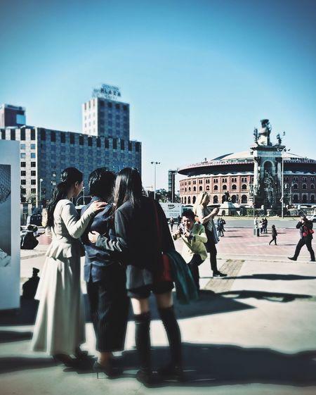 People walking in city against clear sky