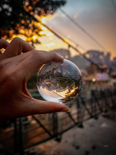 Cropped hand holding crystal ball with bridge reflecting during sunset