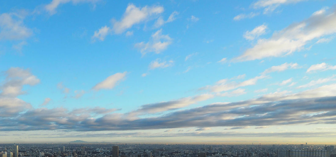 Clear blue sky and white clouds over the city and sunset. Beauty In Nature City; Sky; View; Sunset; Urban; Architecture; Aerial; Blue; Light; Landscape; Exterior; Asia; Downtown; Sunrise; Modern; Background; Travel; Building; Horizon; Looking; Tourism; Cityscape; High; Skyline; Tower; Empty; Over; Clouds; Skyscape Cloud - Sky Day Nature No People Outdoors Scenics Sky Tranquil Scene Tranquility