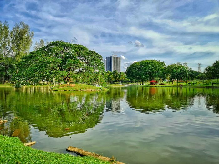 Scenic view of lake by trees and buildings against sky