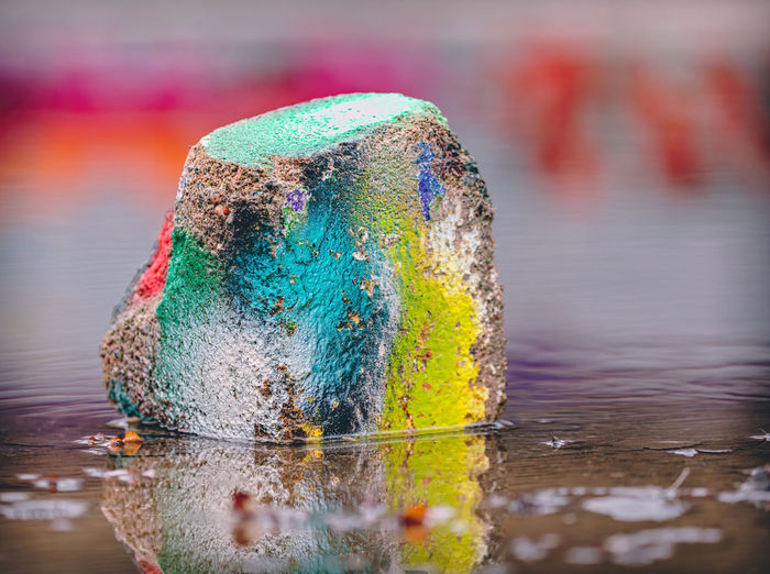 Close-up of multi colored painted rock in puddle