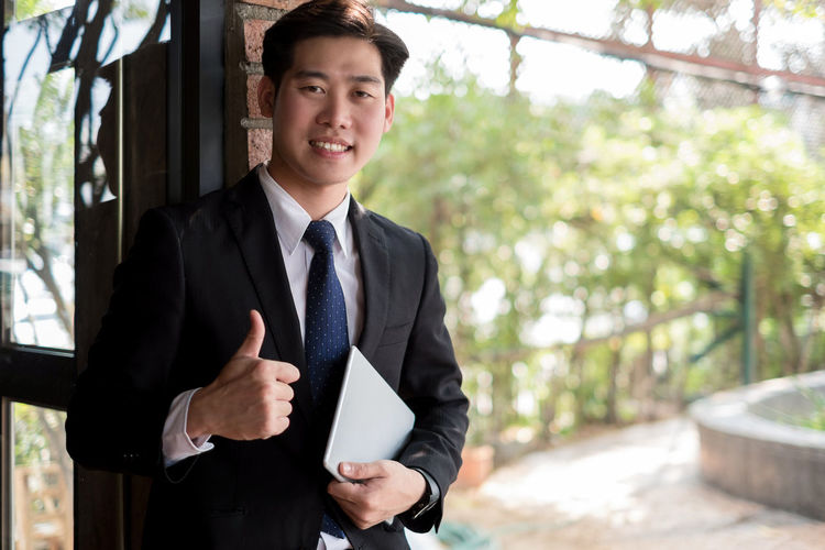 Portrait of smiling young businessman showing thumbs up while holding using digital tablet