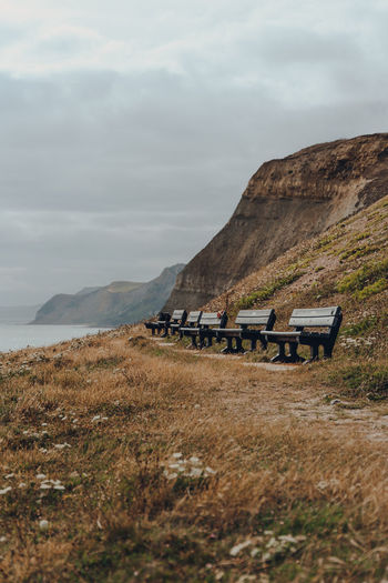 Row of benches along the coastal walk on jurassic coast, a world heritage site in southern england.