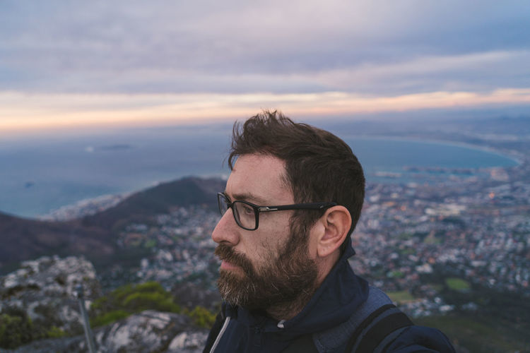 Close-up of man looking away against cloudy sky