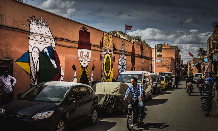 Moroccan Street Art Arch Architecture Art Building Building Exterior Built Structure Car City Cityscape Cloud - Sky Land Vehicle Marrakech Marrakesh Mode Of Transport Morocco Parking People Retail  Sky Street Streetphotography Tradition Transportation Travel Urban