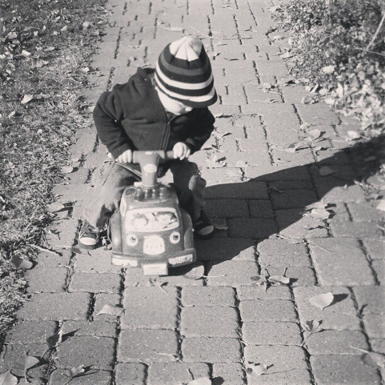 HIGH ANGLE VIEW OF BOY ON COBBLESTONE