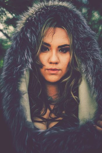 Close-up portrait of young woman wearing fur coat
