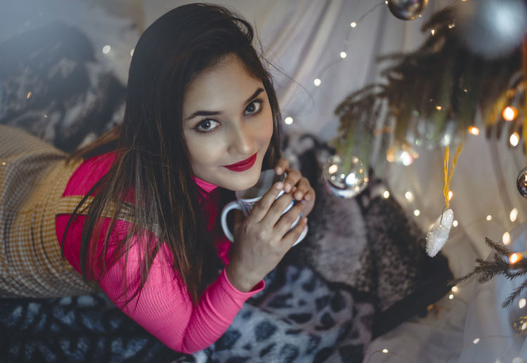 Portrait of beautiful young woman with christmas lights