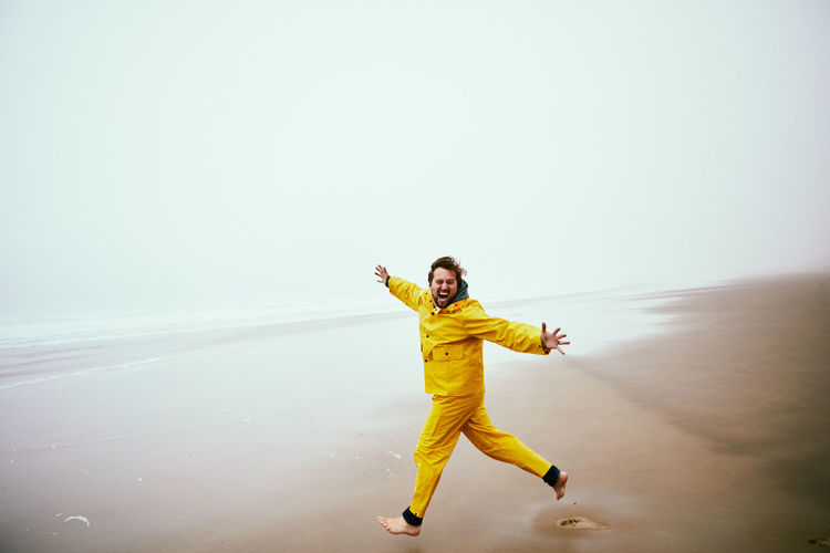 Man running at beach against sky